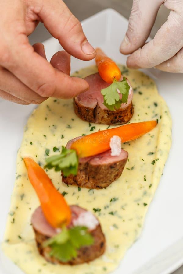 Cuoco unico che decora il piatto della carne fotografie stock libere da diritti