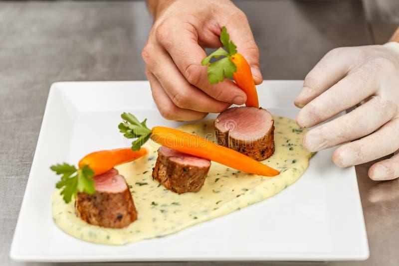 Cuoco unico che decora un filetto di carne di maiale immagini stock