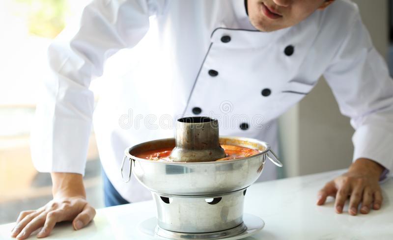 Cuoco unico che esamina e che esamina l'alimento, goong di yum di Tom, stufato di castrato piccante tailandese famoso fotografie stock libere da diritti