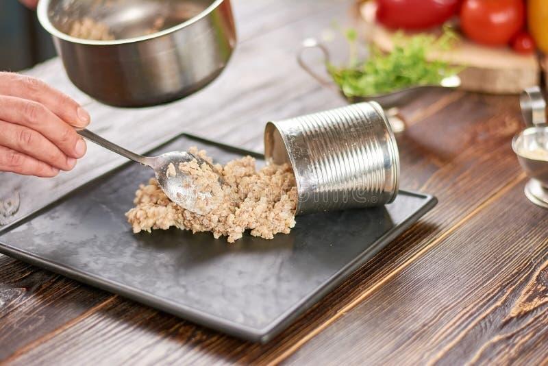 Cuoco unico che mette il porridge dell'orzo perlato sul piatto fotografia stock