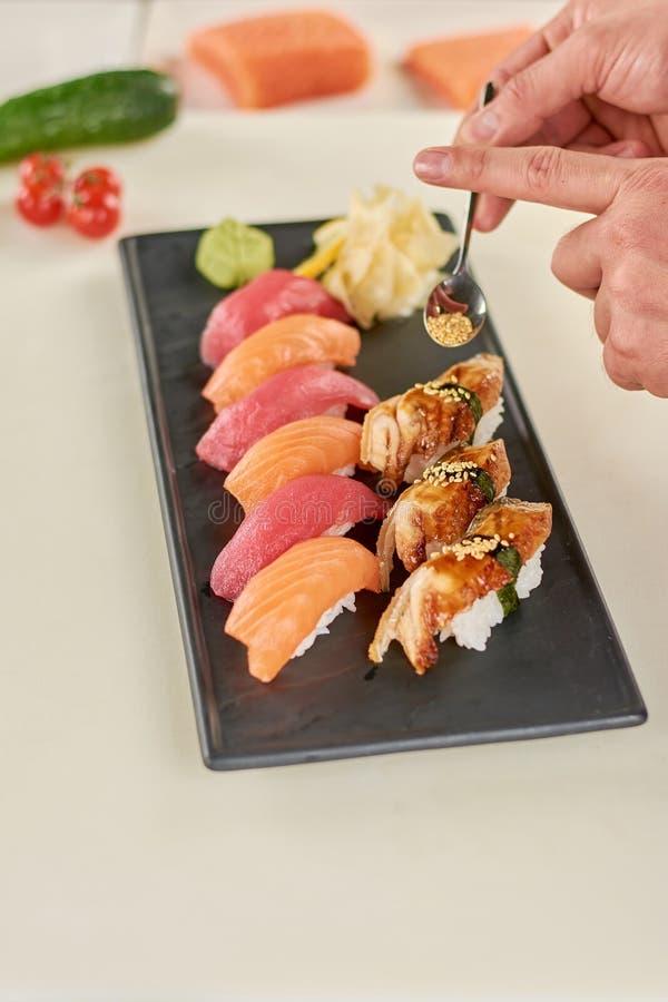 Cuoco unico che mette sesamo sui sushi di nigiri immagini stock