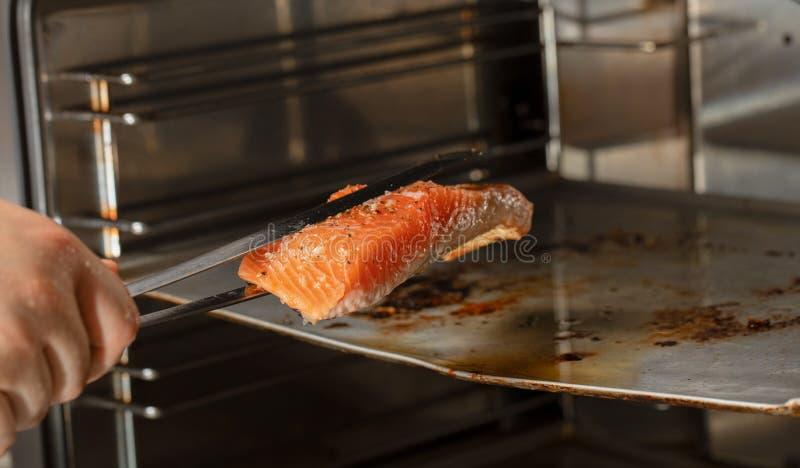 Cuoco unico che prende un raccordo di color salmone perfettamente al forno dal forno La mano che tiene il pesce di color salmone  immagine stock