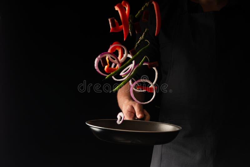 Cuoco unico che prepara le salsiccie delle merguez con i fagiolini, peperoni dolci dolci ed anelli di cipolla rossa, su un fondo  immagine stock libera da diritti