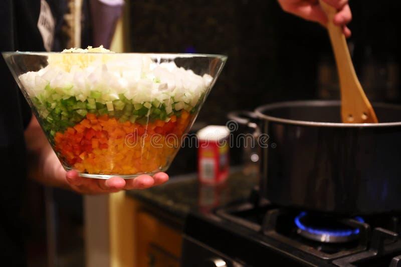 cuoco unico che prepara le verdure alla stufa in una cucina del ristorante fotografie stock