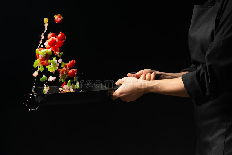 Cuoco unico che prepara le verdure su un fondo scuro su una leccarda immagine stock