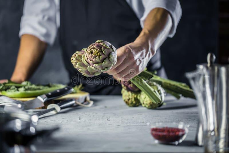Cuoco unico che taglia i carciofi per la preparazione della cena - uomo che cucina dentro la cucina del ristorante immagine stock
