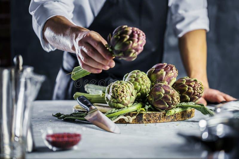 Cuoco unico che taglia i carciofi per la preparazione della cena - uomo che cucina dentro la cucina del ristorante immagini stock