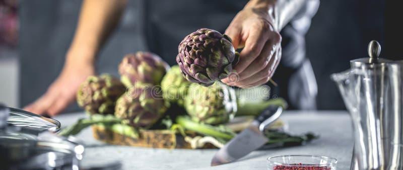 Cuoco unico che taglia i carciofi per la preparazione della cena - uomo che cucina dentro la cucina del ristorante immagini stock libere da diritti
