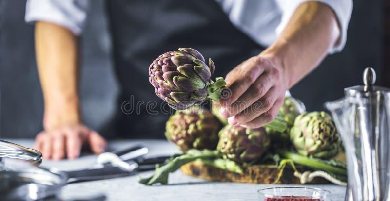 Cuoco unico che taglia i carciofi per la preparazione della cena - uomo che cucina dentro la cucina del ristorante immagine stock libera da diritti