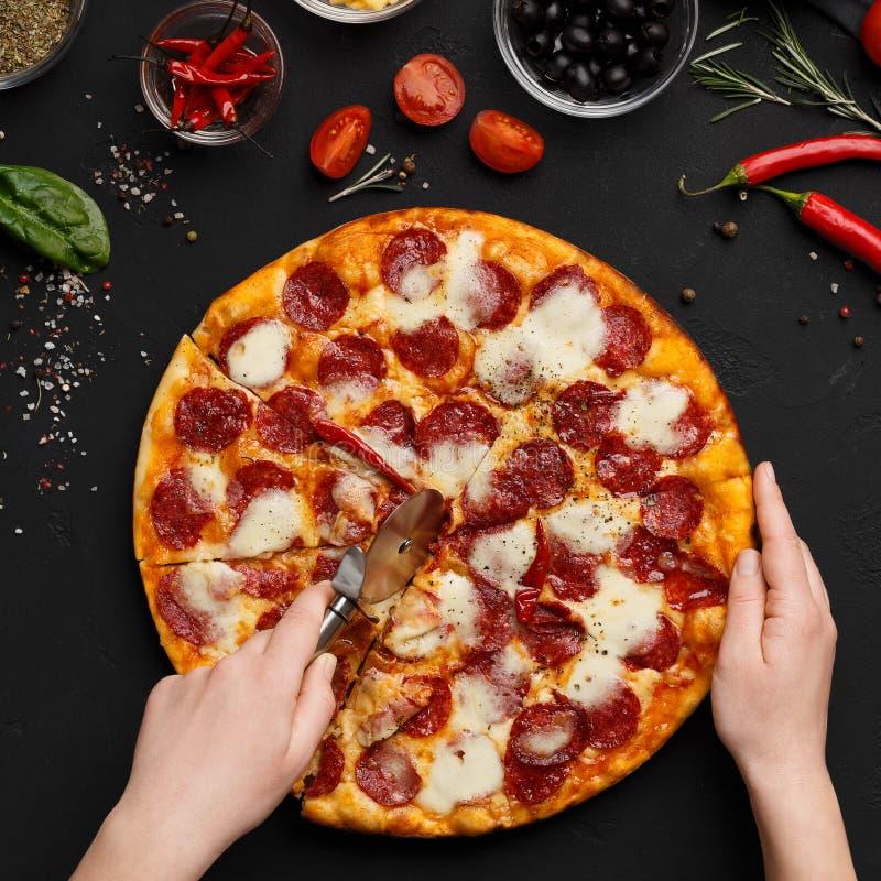 Cuoco unico che taglia pizza appena preparato in fette fotografia stock libera da diritti