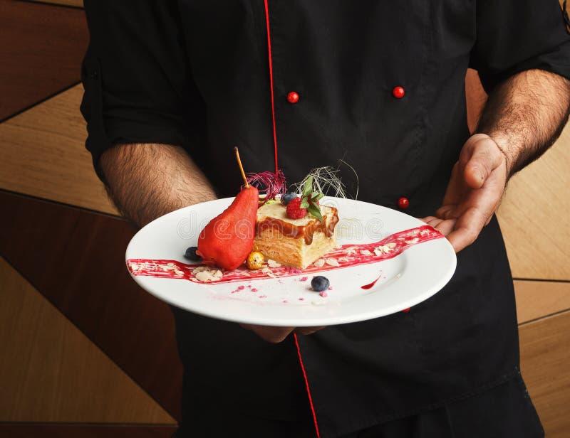 Cuoco unico che tiene il dessert contemporaneo del ristorante fotografia stock libera da diritti