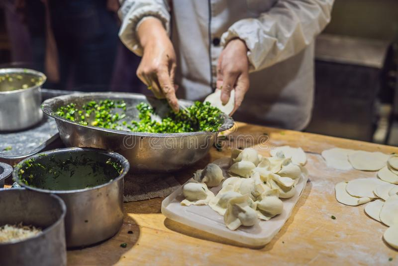 Cuoco unico cinese che produce gli gnocchi nella cucina fotografie stock libere da diritti