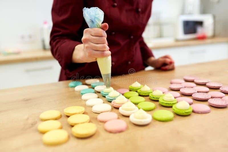 Cuoco unico con l'iniettore che schiaccia riempimento ai macarons fotografia stock