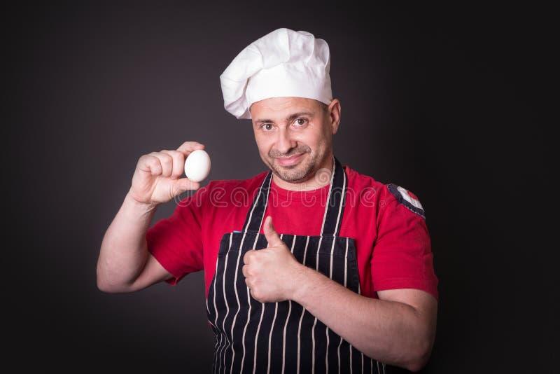 Cuoco unico con l'uovo del pollo in studio su fondo nero fotografia stock