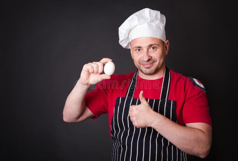 Cuoco unico con l'uovo del pollo in studio su fondo nero immagini stock libere da diritti