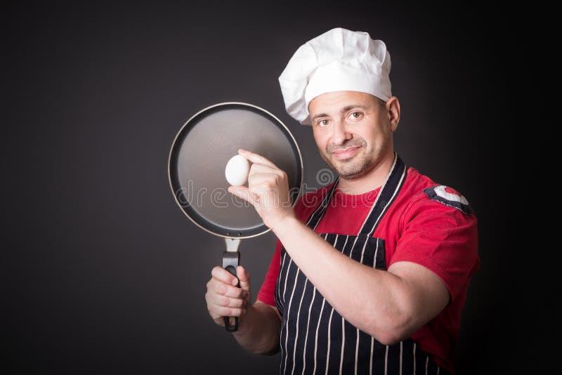Cuoco unico con l'uovo e la padella del pollo in studio su fondo nero immagini stock