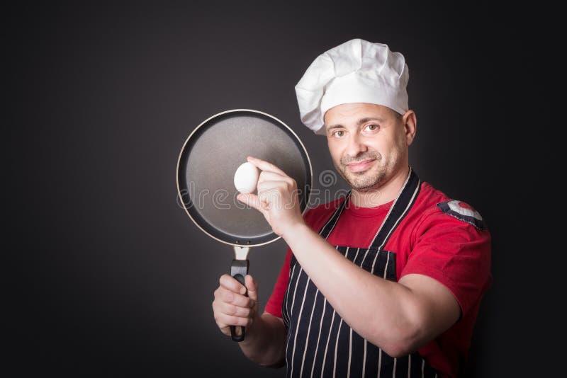 Cuoco unico con l'uovo e la padella del pollo in studio su fondo nero immagine stock