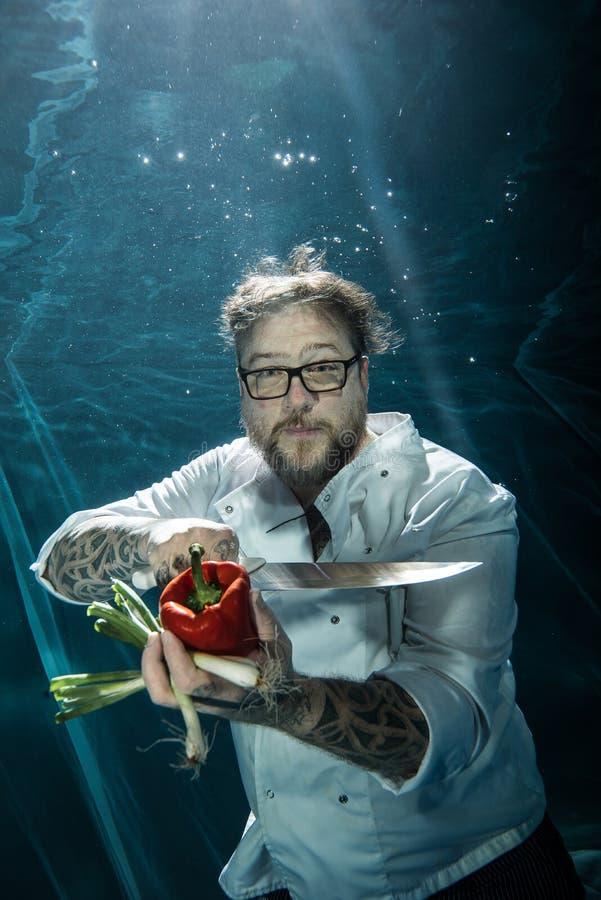 Cuoco unico con le verdure e il kinfe del ` s del cuoco che posa underwater fotografia stock