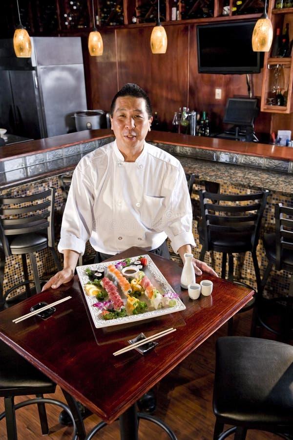 Cuoco unico del ristorante giapponese che presenta il disco dei sushi immagini stock