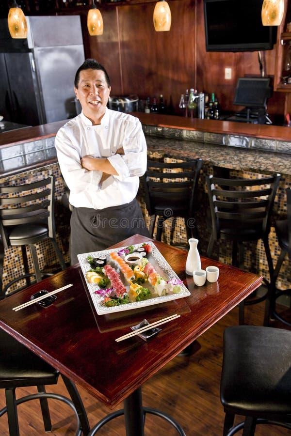 Cuoco unico del ristorante giapponese che presenta il disco dei sushi immagini stock libere da diritti