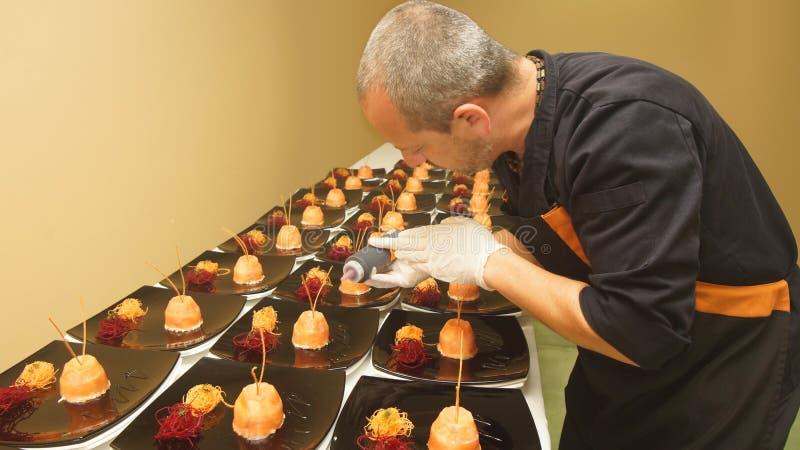 Cuoco unico della cucina professionale che dà gli ultimi tocchi di decorazione ai piatti fotografie stock