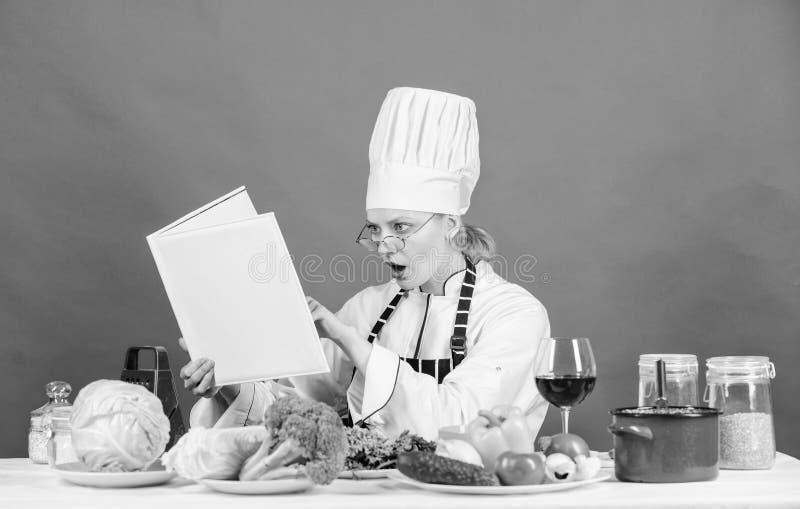 Cuoco unico della donna che cucina alimento sano La ragazza ha letto le migliori ricette culinarie del libro Concetto culinario d immagine stock