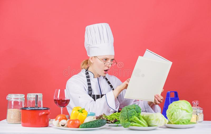 Cuoco unico della donna che cucina alimento sano La ragazza ha letto le migliori ricette culinarie del libro Concetto culinario d immagini stock