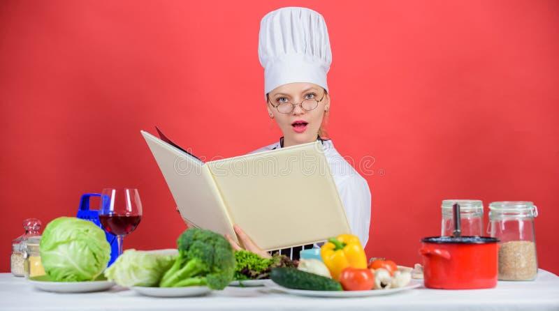 Cuoco unico della donna che cucina alimento sano La ragazza ha letto ricette culinarie superiori del libro le le migliori Cucina  fotografie stock libere da diritti