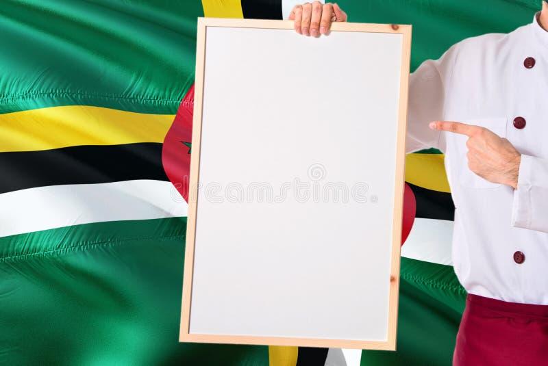 Cuoco unico domenicano che tiene il menu in bianco di lavagna sul fondo della bandiera della Dominica Cucini l'uniforme d'uso che fotografia stock