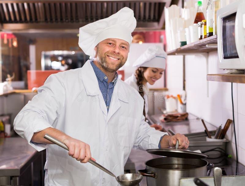 Download Cuoco Unico Ed Il Suo Assistente Alla Cucina Dei Bistrot Immagine Stock - Immagine di felice, dishware: 55358265