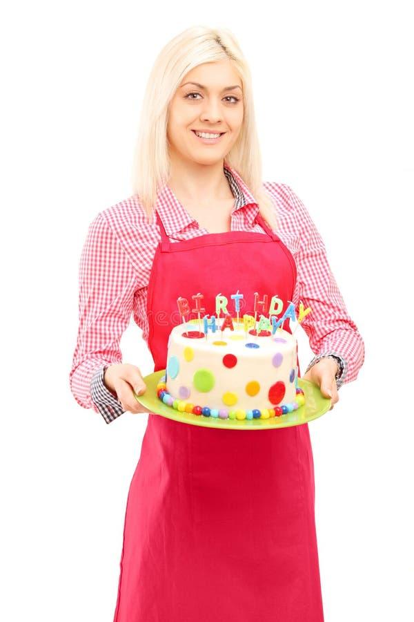 Cuoco unico femminile biondo in grembiule che tiene un dolce delizioso fotografia stock