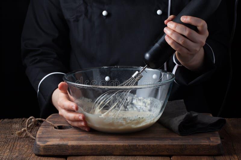 Cuoco unico femminile che mescola la sua pastella con una sbattitura su un fondo nero immagine stock