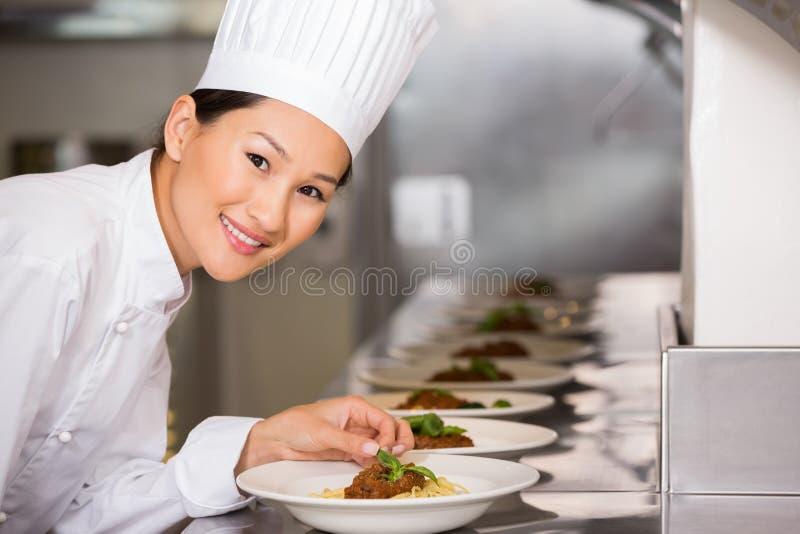 Cuoco unico femminile sorridente che guarnisce alimento in cucina fotografia stock libera da diritti