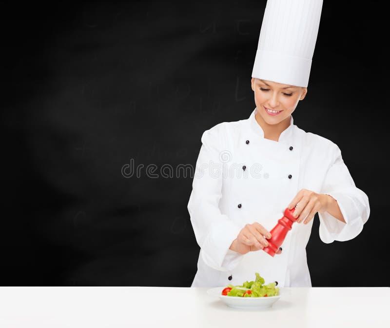 Cuoco unico femminile sorridente con la preparazione dell'insalata fotografie stock libere da diritti
