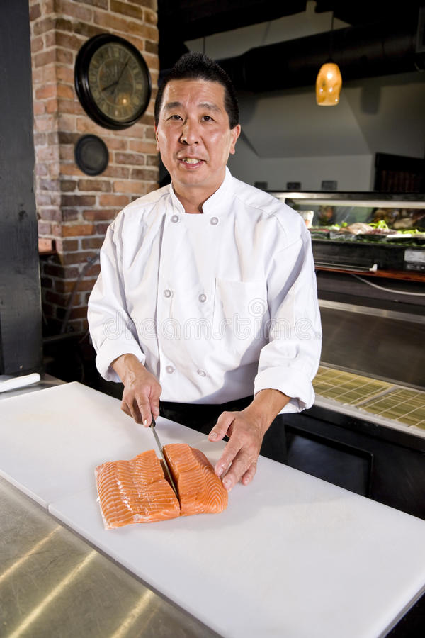 Cuoco unico giapponese che affetta i pesci grezzi per i sushi fotografia stock