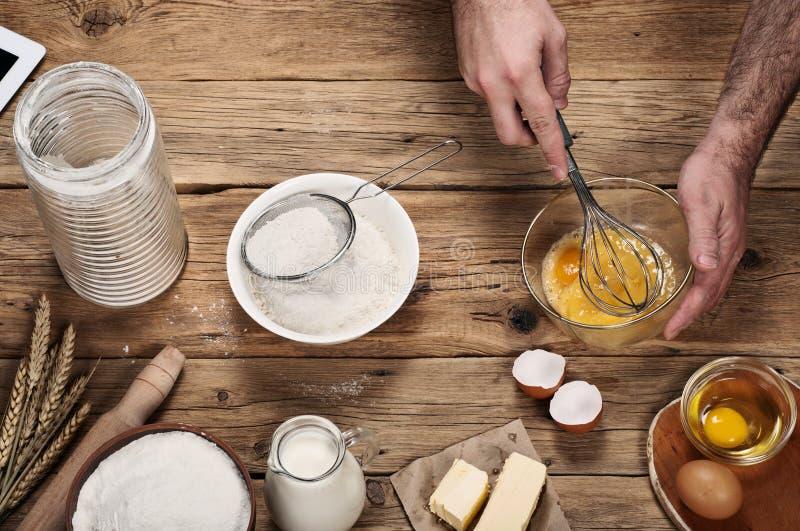 Cuoco unico maschio che monta le uova nel forno sulla tavola di legno fotografia stock