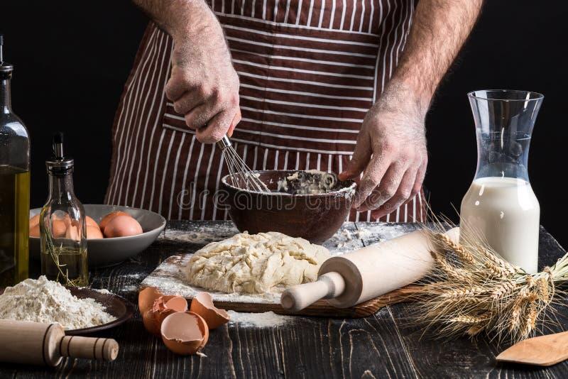 Cuoco unico maschio che monta le uova nel forno sulla tavola di legno Ingredienti per la cottura i prodotti o della pasta della f immagine stock libera da diritti