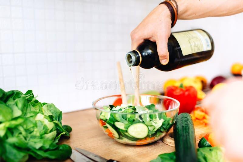 Cuoco unico maschio che prepara insalata, olio d'oliva vergine di versamento sulle verdure fotografia stock libera da diritti