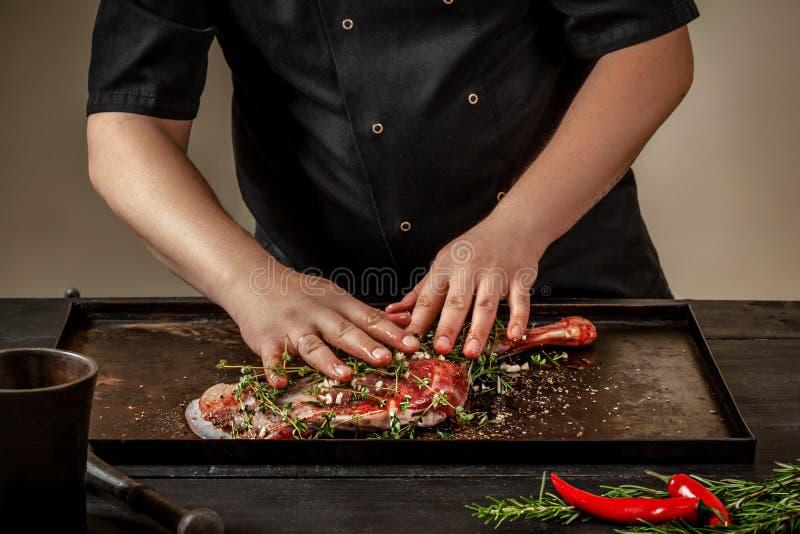 Cuoco unico maschio che sfrega gli stinchi crudi dell'agnello con i verdi e le spezie sul vassoio di pietra sulla tavola di legno fotografie stock