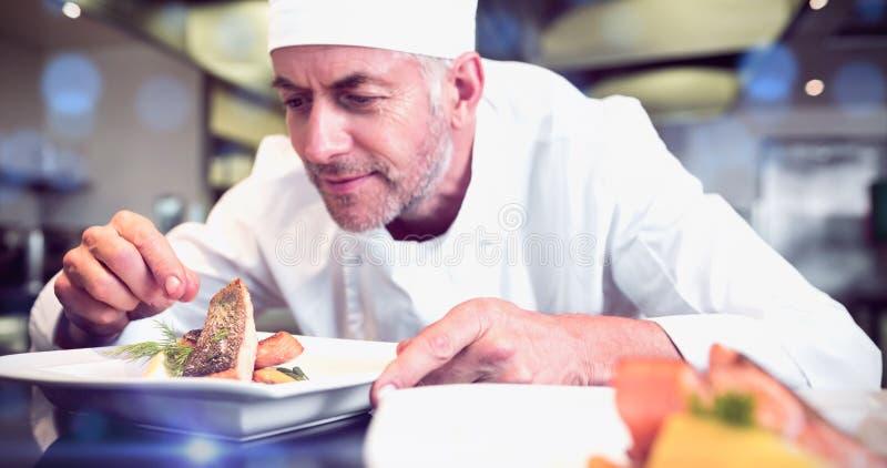 Cuoco unico maschio concentrato che guarnisce alimento in cucina immagine stock