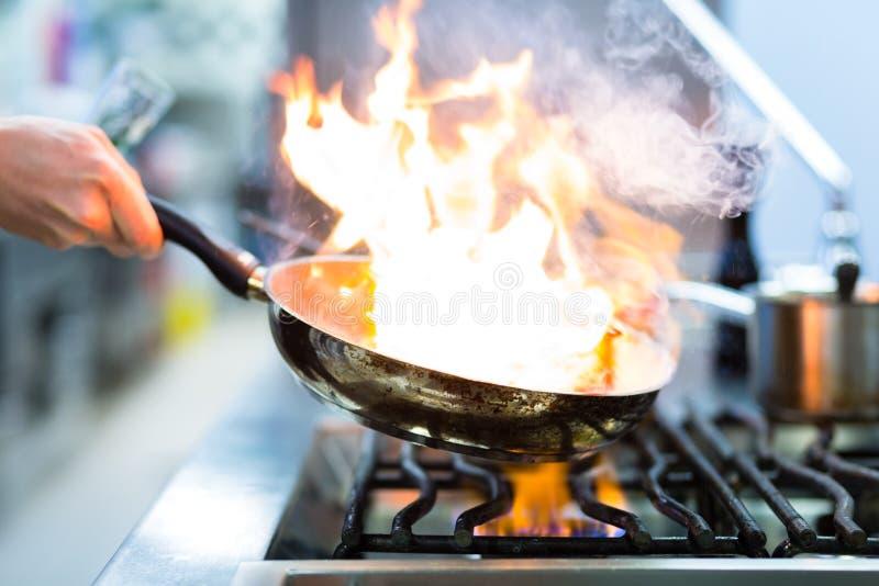 Cuoco unico nella cucina del ristorante alla stufa con la vaschetta fotografia stock libera da diritti