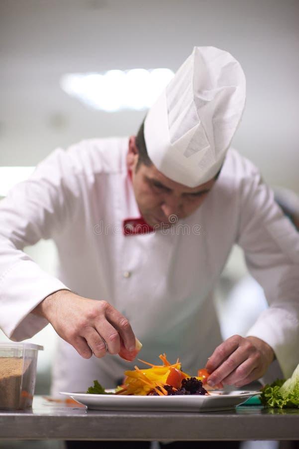 Cuoco unico nella cucina dell'hotel che prepara e che decora alimento fotografia stock