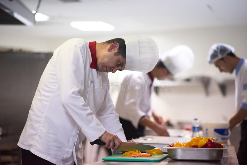 Cuoco unico nelle verdure della fetta della cucina dell'hotel con il coltello fotografia stock libera da diritti