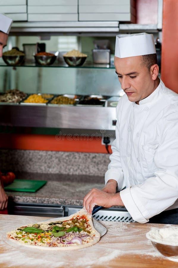 Cuoco unico occupato nella preparazione della pizza fotografie stock libere da diritti