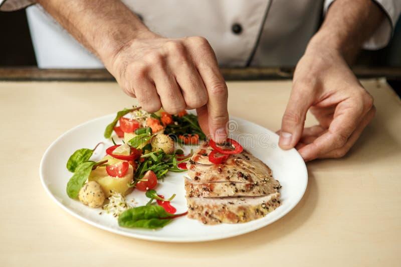 Cuoco unico professionista dell'uomo maturo che cucina pasto all'interno immagini stock