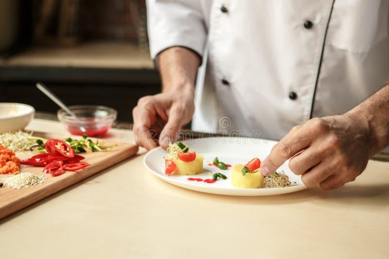 Cuoco unico professionista dell'uomo maturo che cucina pasto all'interno fotografia stock