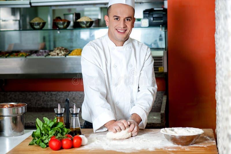 Cuoco unico sorridente che prepara la base della pizza fotografie stock libere da diritti