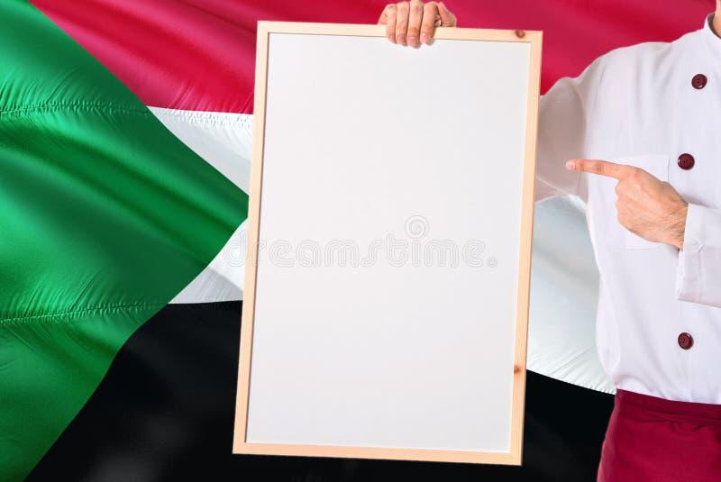 Cuoco unico sudanese che tiene il menu in bianco di lavagna sul fondo della bandiera del Sudan Cucini l'uniforme d'uso che indica fotografia stock
