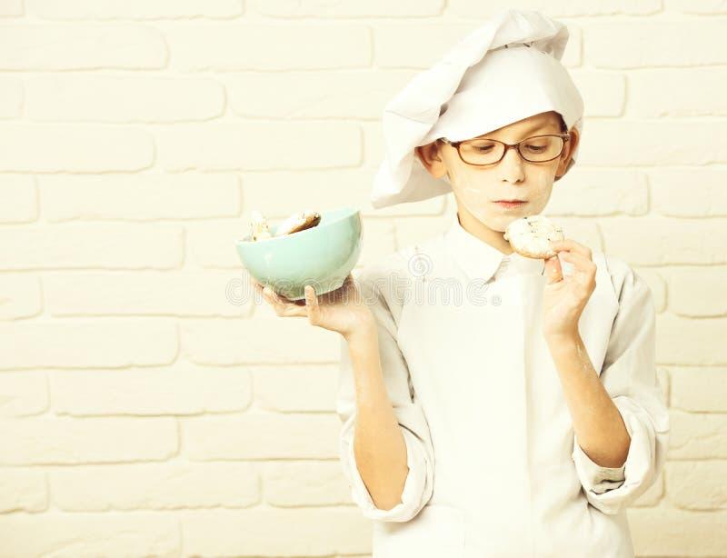 Cuoco unico sveglio del cuoco del giovane bambino piccolo in uniforme e cappello di bianco sulla farina macchiata del fronte con  fotografie stock
