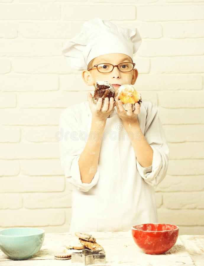 Cuoco unico sveglio del cuoco del giovane ragazzo in uniforme e cappello di bianco sulla farina macchiata del fronte con i vetri  immagine stock libera da diritti